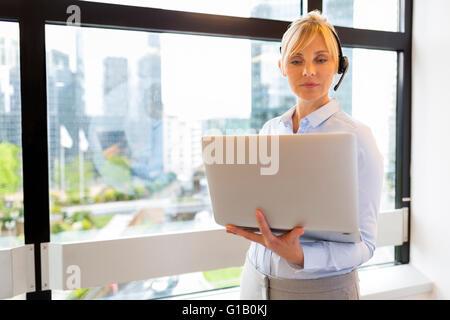 Attraktive Geschäftsfrau, am Laptop arbeiten. Kopfhörer. Gebäude-Hintergrund - Stockfoto