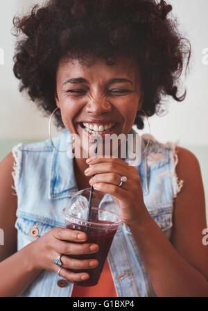 Porträt der fröhliche junge Frau trinken Saft aus frischen Früchten und lächelnd hautnah. Glückliche junge afrikanische weibliches Modell mit einem drin
