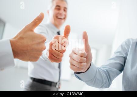 Fröhlich Geschäftsleute Daumen nach oben, die Hände nah oben, Erfolg, Leistung und Zufriedenheit Konzept - Stockfoto