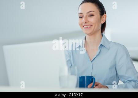 Lächelnde junge Frau hält eine Tasse Kaffee und eine Pause am Schreibtisch sitzen - Stockfoto