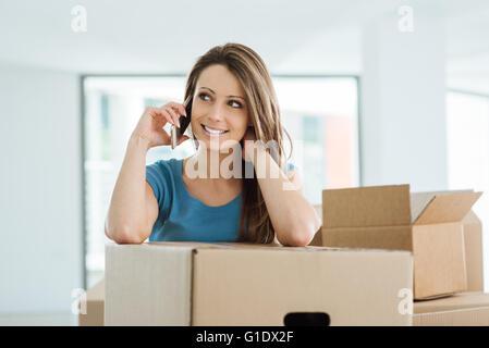 Schöne junge Frau mit einem Anruf in ihrem neuen Haus, sie lehnt sich auf einen Karton - Stockfoto