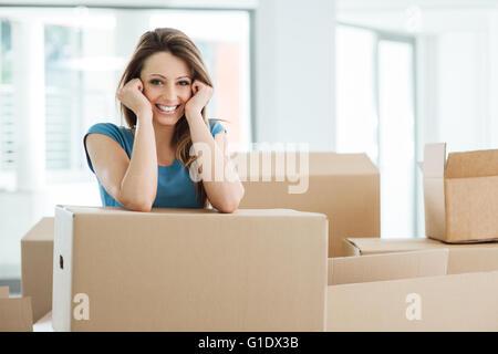 Lächelnde junge Frau bewegt sich in ihrem neuen Haus und stützte sich auf einen Karton - Stockfoto