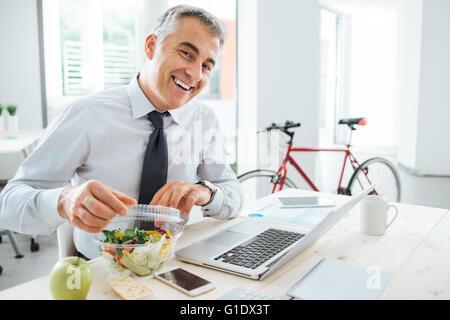Glücklich Kaufmann brechen seinen Salat Pack öffnen und mit einem Mittagessen am Schreibtisch - Stockfoto