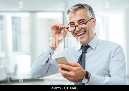 Lächelnd Geschäftsmann mit Sehprobleme, wird er seine Brille anpassen und etwas auf seinem Handy zu lesen - Stockfoto