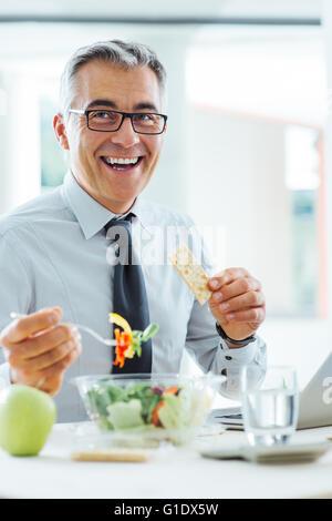 Lächelnd Geschäftsmann am Schreibtisch sitzen und mit einer Mittagspause, isst er eine Salatschüssel - Stockfoto