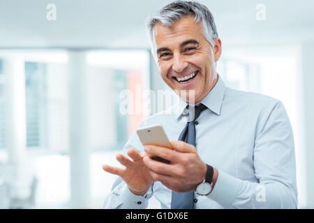 Fröhliche Geschäftsmann mit einem Touch Screen Smartphone und Blick in die Kamera Lächeln - Stockfoto
