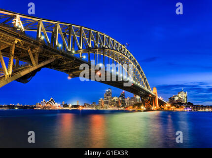 Seitenansicht der Sydney Harbour Bridge in Richtung Stadt CBD, die Felsen und Circular Quay bei Sonnenuntergang - Stockfoto