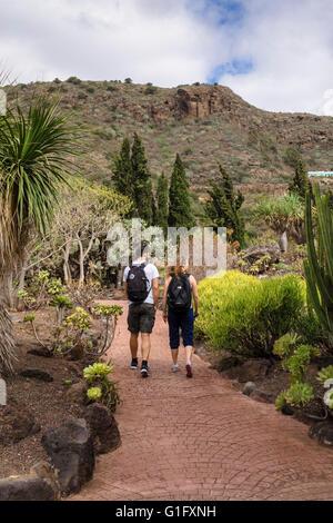 Rückansicht des Touristen zu Fuß durch den Kaktusgarten (Jardín de Cactus y Sucelentas) im Botanischen Garten von - Stockfoto