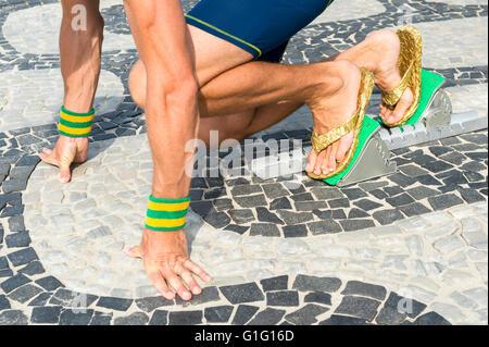 Brasilianische Sportler tragen Flip-Flops hockend an der Startposition im laufenden Blöcken auf den Fliesen von - Stockfoto