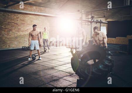 Passen Sie jungen Mann mit kein Hemd Spiegeln eines Reifens, trainieren Sie im Fitnessraum mit anderen Menschen - Stockfoto
