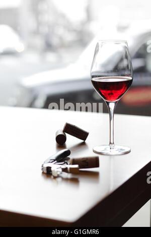Weinglas im Zentrum von London mit schwarzen Taxi außerhalb und einen Korkenzieher und Korken auf dem Tisch. - Stockfoto