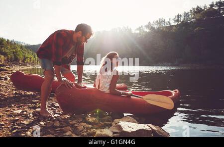 Junger Mann schiebt eine Kanu in das Wasser, während eine Frau sitzt auf dem Kanu. Paar für Kajak in See an einem - Stockfoto