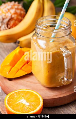 Smoothie mit tropischen Früchten: Mango, Banane, Ananas im Weckglas Mason auf dem alten hölzernen Hintergrund - Stockfoto