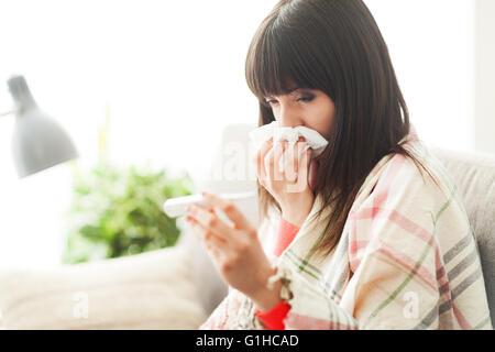 Junge Frau mit Erkältung und Grippe krank, sie ist ihre Nase und ihre Körpertemperatur messen - Stockfoto