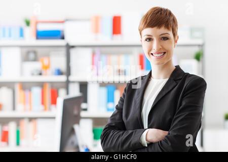 Erfolgreiche junge Geschäftsfrau in ihrem Büro, sie posieren und lächelt in die Kamera - Stockfoto
