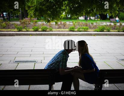 paar in der Liebe auf einer Bank sitzen und küssen. - Stockfoto