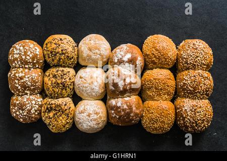 Handwerkliche Bäckerei Brötchen und Gebäck auf dunklem Schiefer Hintergrund von oben - Stockfoto