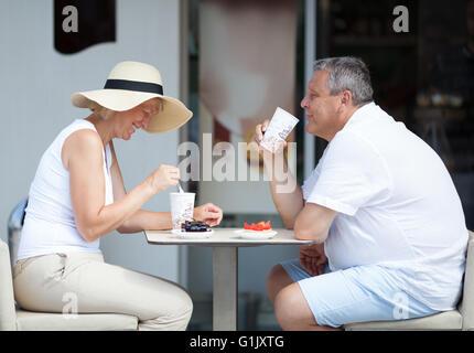 Paar genießt Kaffee und Desserts auf Cafe-Terrasse - Stockfoto