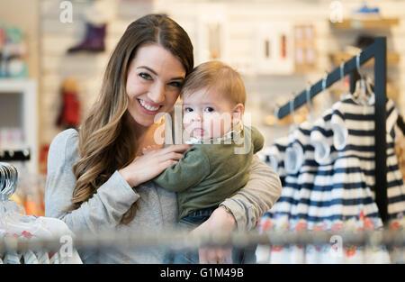 Kaukasische Mutter und Baby Sohn Einkaufen in Bekleidungsgeschäft - Stockfoto