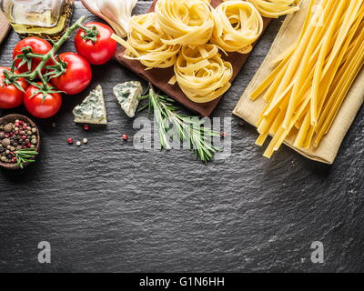 Pasta Zutaten. Cherry-Tomaten, Spaghetti Nudeln, Rosmarin und Gewürze auf einem Graphit-Brett. - Stockfoto