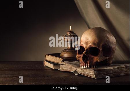 Menschlicher Schädel, Kerze angezündet und alten Buch auf einem alten hölzernen Tisch, wissen und Allgemeinbildung - Stockfoto