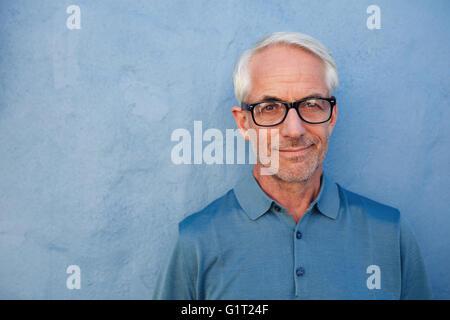 Nahaufnahme, Porträt von schöner senior Mann mit Brille, Blick in die Kamera, er steht vor einer blauen Wand. - Stockfoto