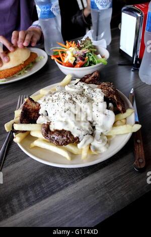 Ein Teller mit Steak mit Pilzsauce und Pommes Frites mit einer Schüssel griechischen Salat und Huhn Schnitzel Burger - Stockfoto