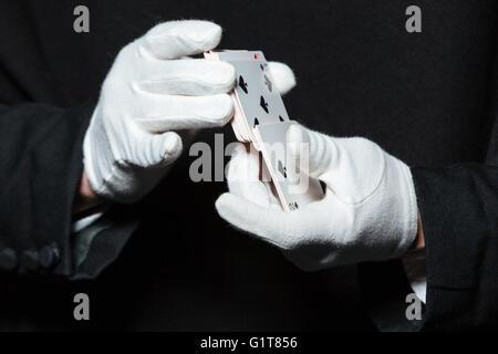 Nahaufnahme der Hände des Magiers der Mann in weiß Handschuhe schlurfenden Spielkarten auf schwarzem Hintergrund - Stockfoto