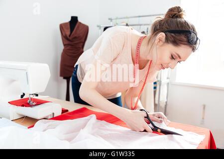 Schöne konzentriert junge Frau Modedesigner schneiden weißen Stoff im studio - Stockfoto