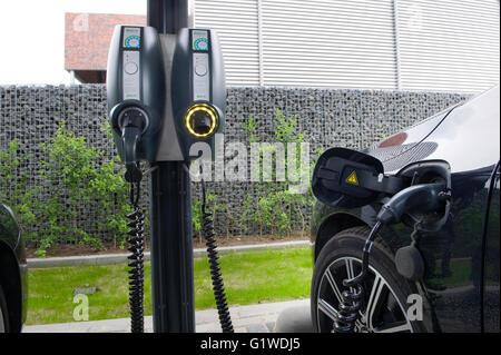 Ein Elektroauto wird auf einem Parkplatz geparkt und ist an ein Kraftwerk aufgeladen wird. - Stockfoto