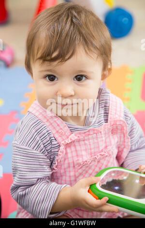 Porträt von liebenswert einjähriges Babymädchen mit Spielzeug in Händen und lächelnd entfernt - Stockfoto