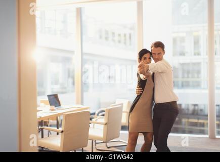Unternehmer und Unternehmerin tanzen im Konferenzraum - Stockfoto