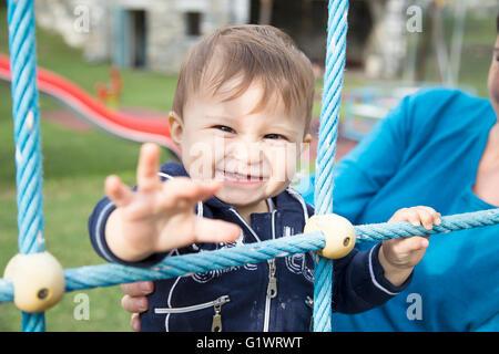 Einjähriges Mädchen zieht ihren Arm und lächelt in die Kamera - Stockfoto