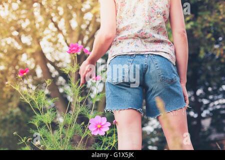 Eine junge Frau pflückt Blumen auf einer Wiese im Sommer - Stockfoto