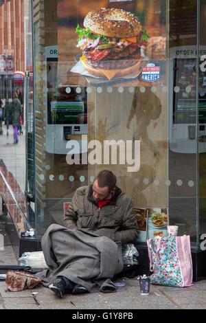 Eine Obdachlose rough sleeper Mann in den Bürgersteig in schlechtem Zustand sitzt in Liverpool, Merseyside, UK - Stockfoto