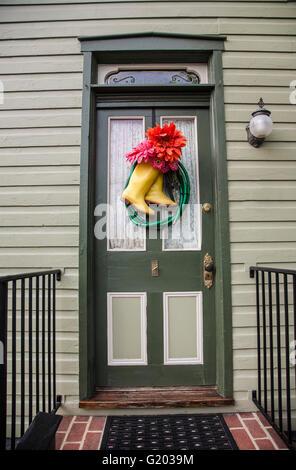 Gelbe Farbe regen Stiefel und Wasserschlauch und Blumen auf einem Haus Feder Tür Kranz, Lancaster County, Pennsylvania, - Stockfoto