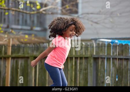 Kind Kleinkind Mädchen springen auf einem Spielplatz im Hinterhof Latein Ethnizität - Stockfoto