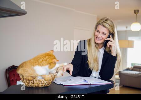 Geschäftsfrau petting eine Katze in einem Weidenkorb, lächelnd, und sprechen auf einem Telefon. - Stockfoto