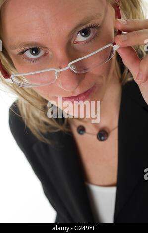 Geschäftsfrau, die über den Rand ihrer Brille - Stockfoto