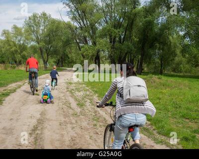 Familie Radfahren entlang der Straße in einer ländlichen Gegend - Stockfoto