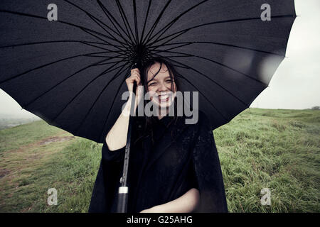 Porträt von lächelnden Frau Holding Regenschirm im wind - Stockfoto