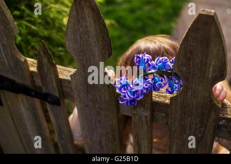 Mädchen mit Hyazinthenblumen Holztor im Garten stehen - Stockfoto
