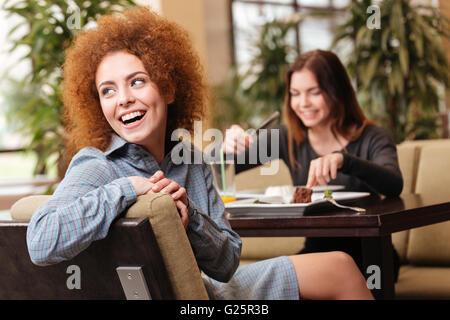 Zwei fröhliche schönen jungen Frauen im Café sitzen und gemeinsam lachen - Stockfoto
