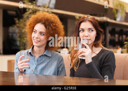 Zwei hübsche junge Frauen sitzen im Café und Trinkwasser - Stockfoto