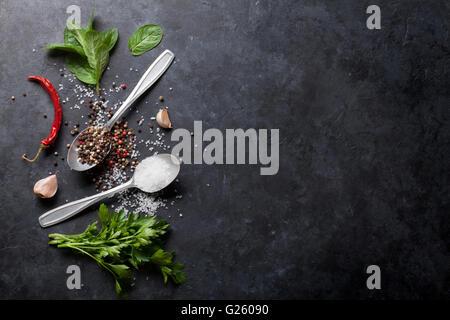 Schwarzen, weißen und roten Pfeffer und Salz Gewürze in Löffel. Minze und Petersilie Kräuter. Draufsicht mit Textfreiraum - Stockfoto