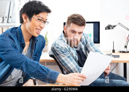 Zwei schöne nachdenkliche junge Männer sitzen und arbeiten mit Dokumenten in office - Stockfoto