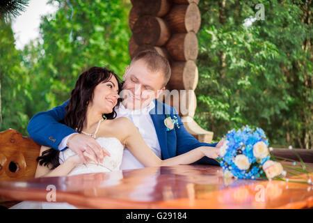 Braut und Bräutigam genießen Mahlzeit bei Hochzeitsfeier Sommerpark - Stockfoto
