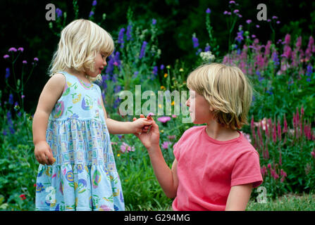Zwei Mädchen (Schwestern) in einem Garten mit Blick auf Blumen, Blumen in Missouri - Stockfoto