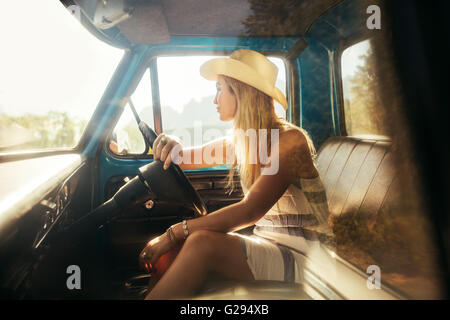 Portrait von junge Frau sitzt auf dem Fahrersitz eines Autos und wegsehen. Mädchen mit Hut auf einem Roadtrip. Stockfoto