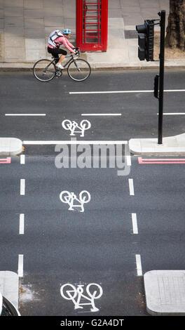 Eine Luftaufnahme eines Radfahrers in ein Radweg vorbei an eine rote Telefonzelle mit drei Zyklus-Zeichen auf dem - Stockfoto